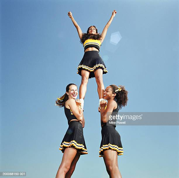 two cheerleaders lifting squad member in air, portrait, low angle - pyramid stock pictures, royalty-free photos & images