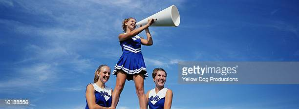 two cheerleaders supporting third cheerleader with megaphone - cheerleader up skirt stock photos and pictures