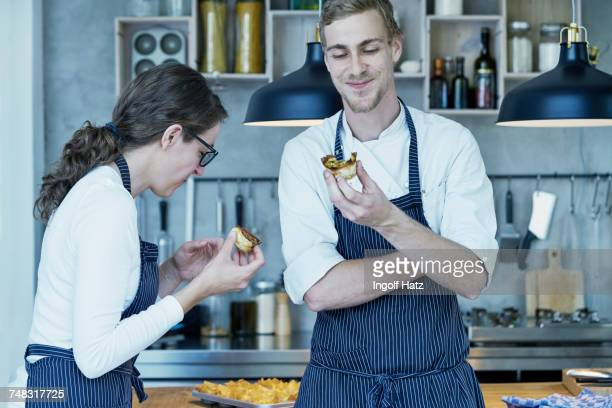 Two chefs in kitchen, tasting freshly baked canapes