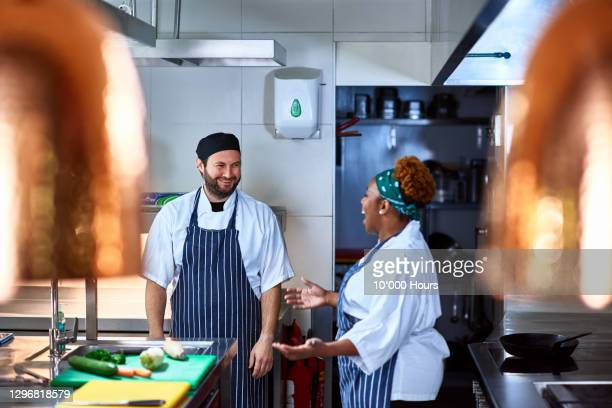 two chefs talking and laughing in commercial kitchen - food and drink industry stock pictures, royalty-free photos & images
