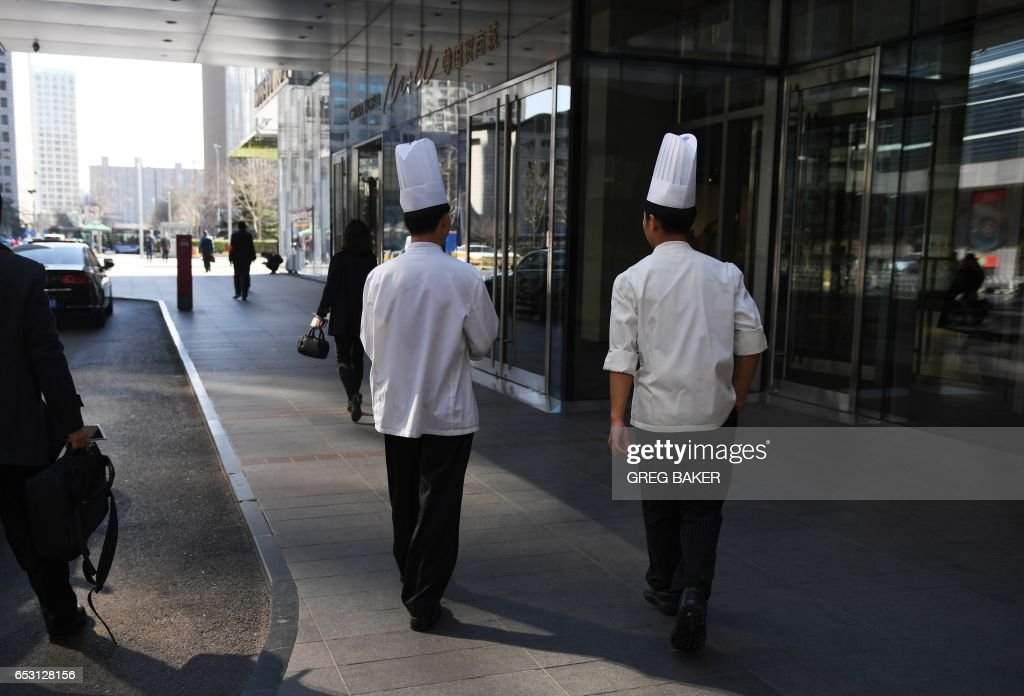 Two chefs walk outside a shopping mall in Beijing on March 14, 2017. China retail sales growth decelerated to 9.5 percent year-on-year in January and February, government data showed on March 14, a...