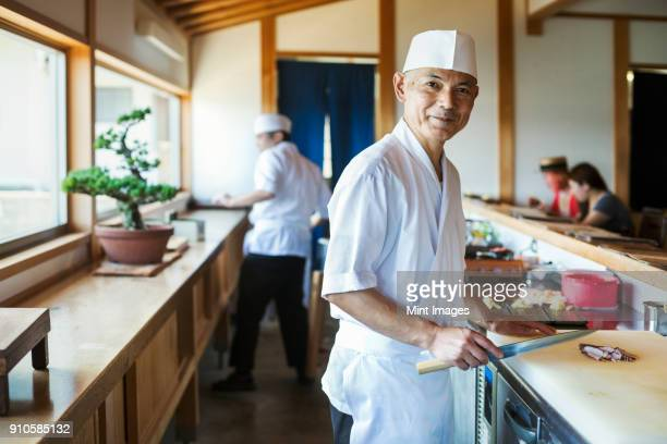 two chefs working at a counter at a japanese sushi restaurant. - japanese culture stock pictures, royalty-free photos & images