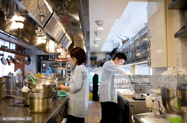 Two chefs working in kitchen, side view