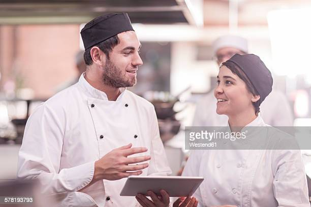 Two chefs working together in kitchen, using digital tablet