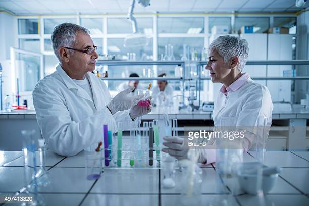 Two chemists communicating in a laboratory while working on expe