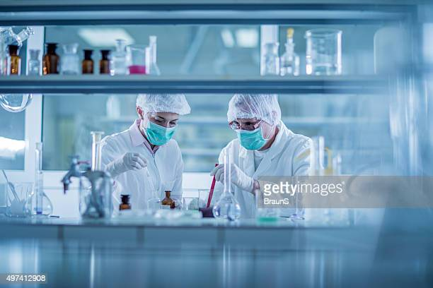 Two chemists examining chemicals for their scientific research in laboratory.