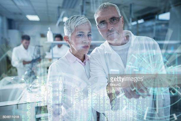 Two chemists working on digitally generated image on touch screen.