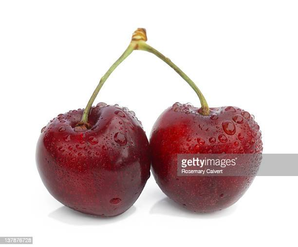 two cherries joined by stalks, with water drops - juicy stock pictures, royalty-free photos & images