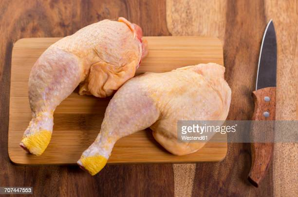 two chicken legs on chopping board - chicken leg stock photos and pictures