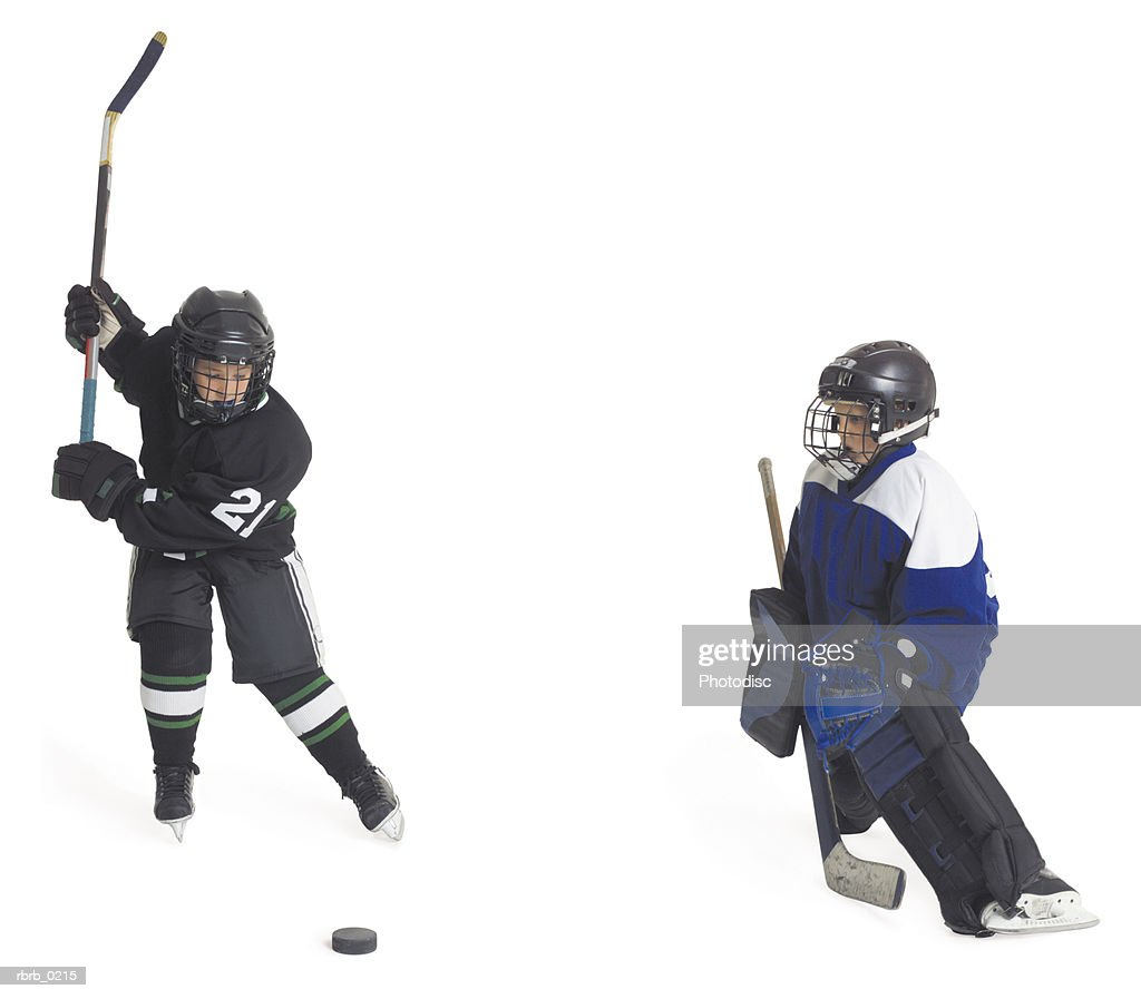 two child caucasian male hockey players on opposing teams face off as one prepares to shoot as the goalie gets ready to block : Stockfoto
