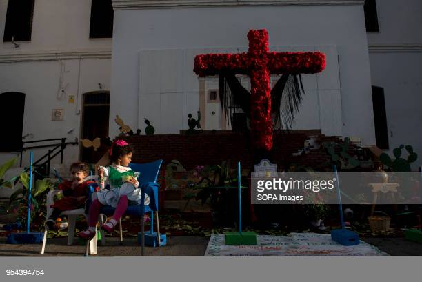Two child sit in front of a crooss during the Dia de la Cruz El día de la Cruz or Día de las Cruces is one of the most beautiful festivities in...