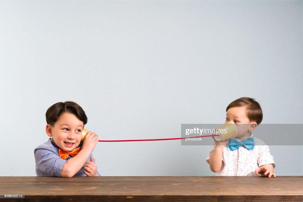 Due bambini stanno usando tazze di carta come telefono : Foto stock