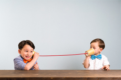 Two childeren are using paper cups as a telephone 946040214