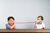 Two childeren are using paper cups as a telephone