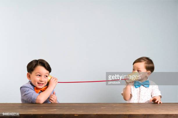 two childeren are using paper cups as a telephone - parlare foto e immagini stock