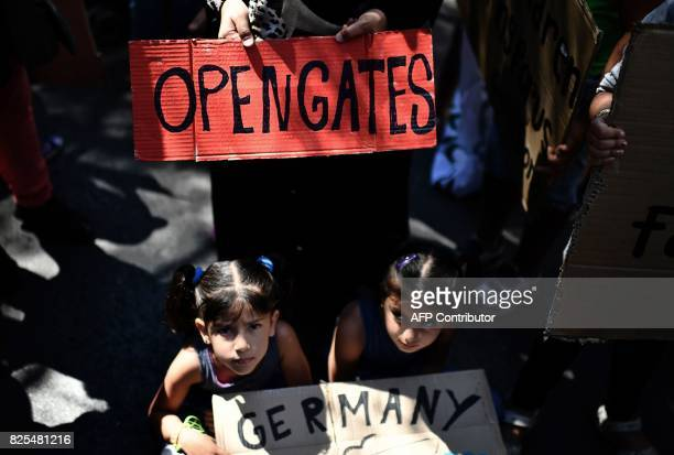 Two children and a woman pose with their placards as they take part in a demonstration in central Athens outside the German embassy with others...