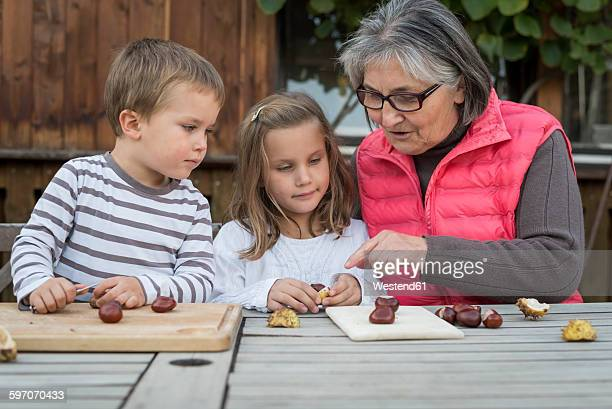 Two children and their grandmother tinkering with chestnuts