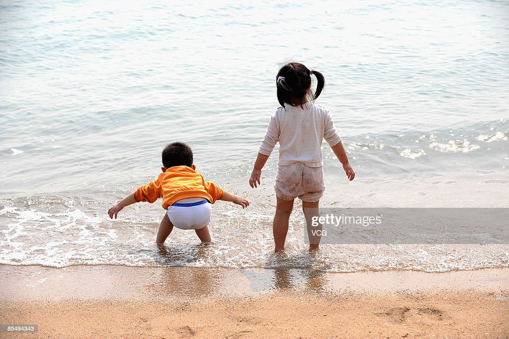 Two children are seen playing at a beach on March 18, 2009 in Xiamen, Fujian Province of China. The uprising temperature marks the coming of spring.
