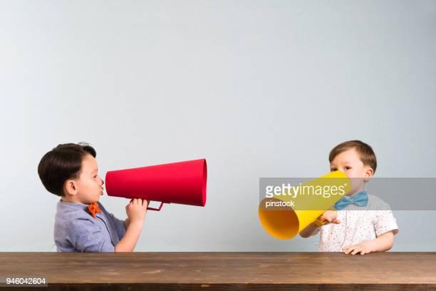two children are talking with paper megaphone - megaphone imagens e fotografias de stock