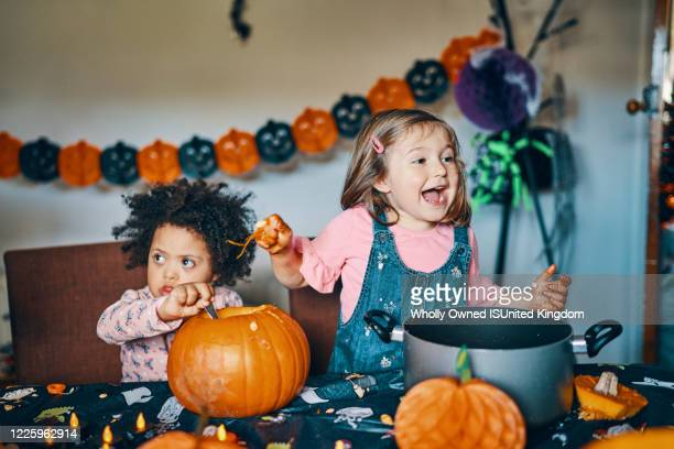 two children at a table with a pumpkin taking out the middle and laughing. - halloween stock pictures, royalty-free photos & images