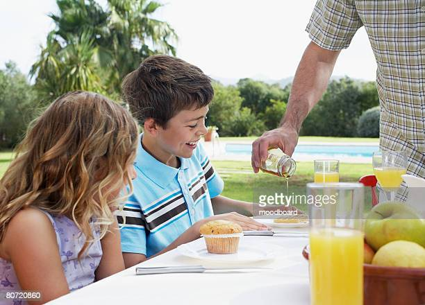 Two children at table (6-11) father pouring syrup