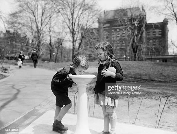 Two Children at Water Fountain in Park Washington DC USA circa 1924