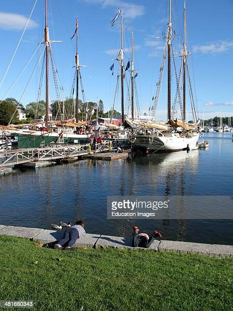 Two children at waters edge Camden Harbor Maine Coast New England USA