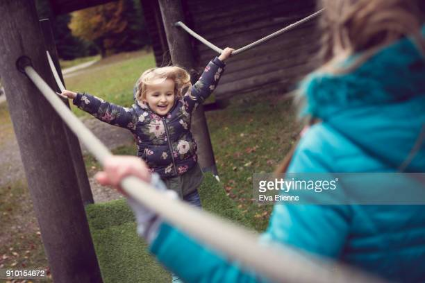 Two children balancing on play equipment on a woodland walk