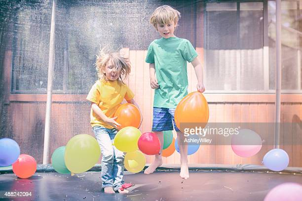 Two children bounce on a trampoline surrounded by balloons