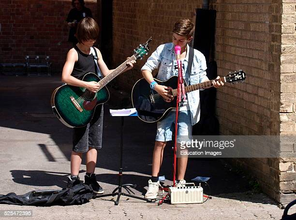 Two Children Busking on the streets of Cirencester Gloucestershire UK