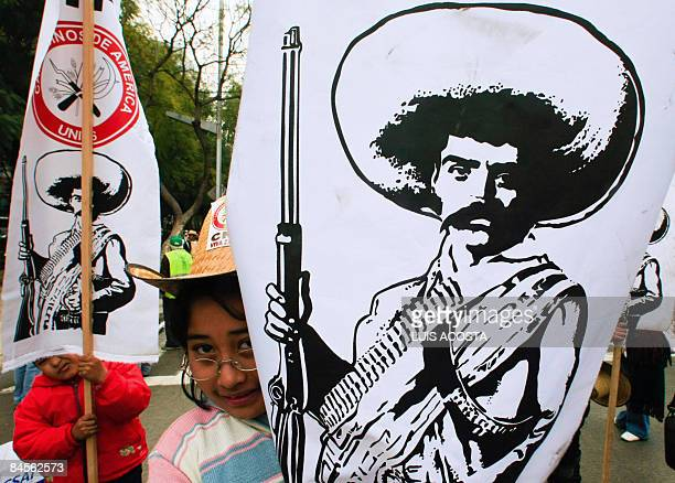 Two children carry banners of Mexican revolutionary leader Emiliano Zapata during a march of peasants against the economic model of Mexican President...