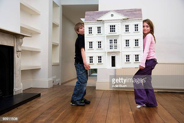 two children carrying a dollhouse - carrying stock pictures, royalty-free photos & images