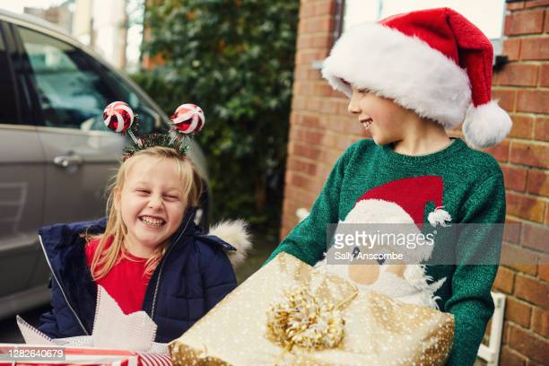 two children carrying christmas presents - sally anscombe stock pictures, royalty-free photos & images