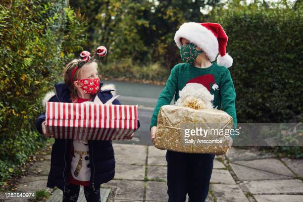 two children carrying christmas presents - coronavirus winter stock pictures, royalty-free photos & images