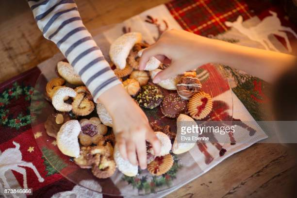 two children choosing traditional german christmas cookies - indulgence stock pictures, royalty-free photos & images