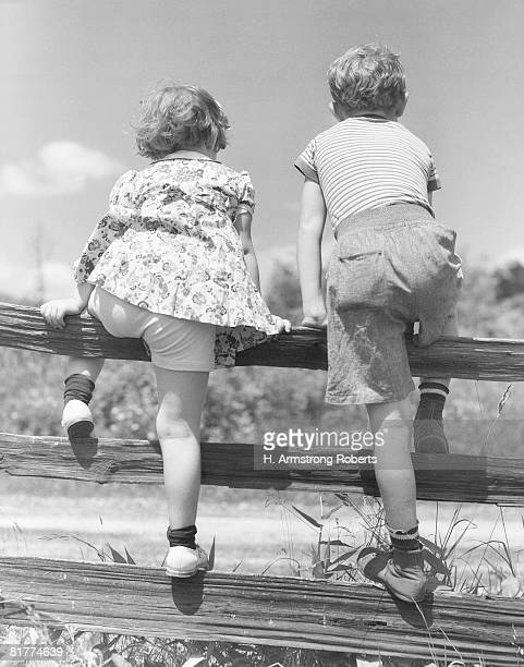two children climbing over split rail fence, rear view. - dress over pants stock pictures, royalty-free photos & images