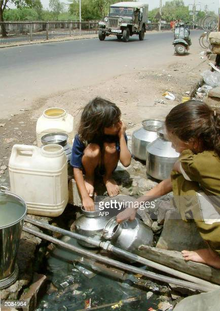 Two children collect what they will use as 'domestic water' from a leaking pipe linked to a sewage line in Bhopal 04 June 2003 on the eve of ' world...