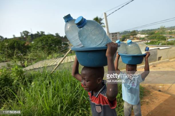 Two children come back from the well carrying with bottles of water in the popular district of Yopougon where inhabitants lack of of drinking water...