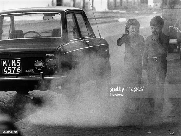 Two children cover their faces against exhaust fumes from traffic in Milan January 1973