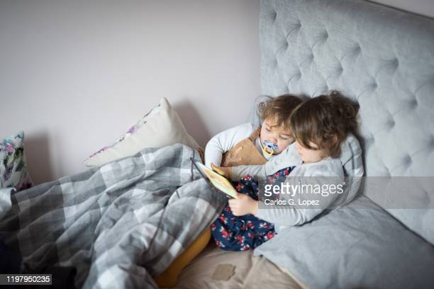 two children cozily watching their digital tablet in bed under the duvet - watching stock pictures, royalty-free photos & images