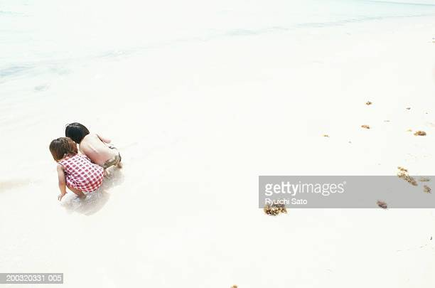 Two children (2-3) crouching on beach, elevated view