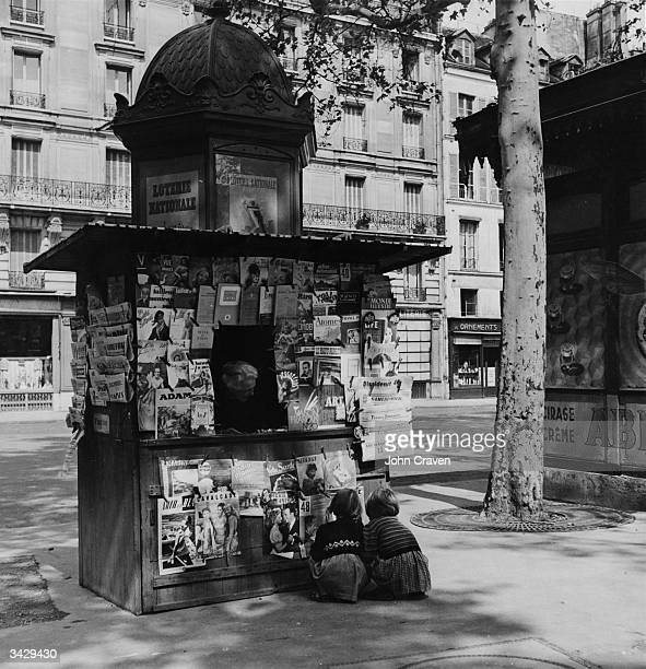 Two children crouching to examine the magazines at a Paris street kiosk