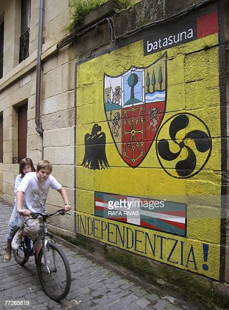 Two children cycle past graffiti signed by proindependence banned Basque party Batasuna political wing of ETA demanding independence for the Basque...