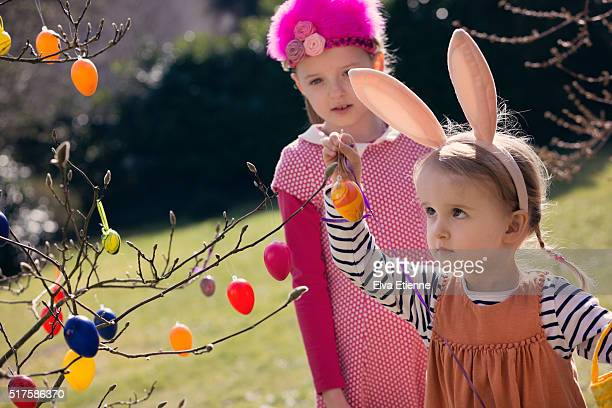 Two children decorating tree with Easter eggs