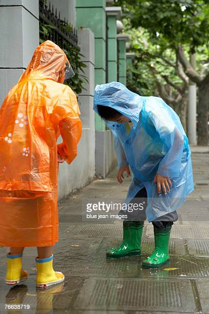 Two children discover puddles on a rainy day.
