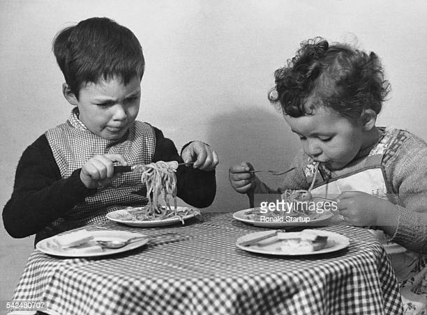 Two children doing their best to eat a meal of spaghetti May 1952 Original publication Picture Post 5865 There's Simply No End To It pub 17th May 1952