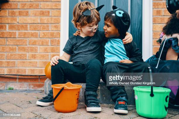 two children dressed for halloween with their arms around each others shoulders. - halloween stock pictures, royalty-free photos & images