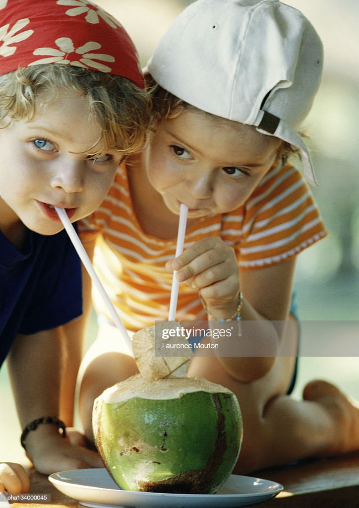 Two children drinking fresh juice through straws, close-up : Stockfoto