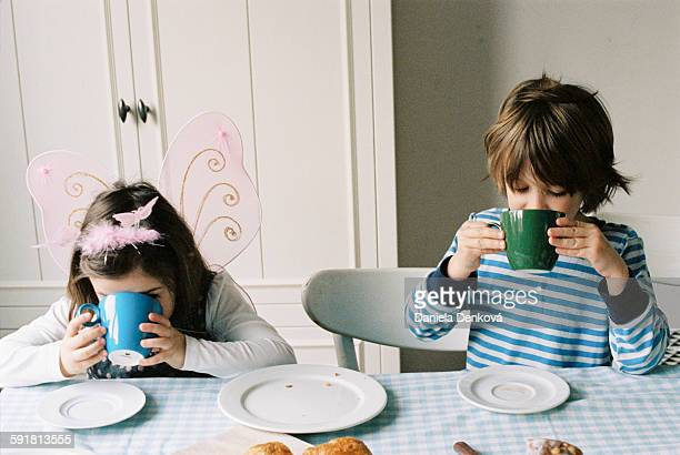 Two children drinking hot cocoa