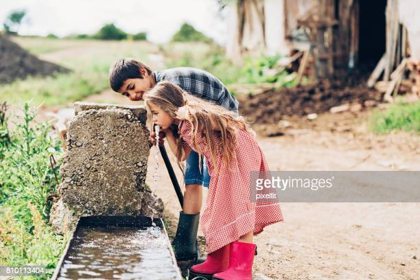 Two children drinking water outdoors